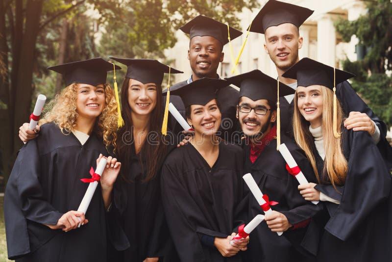 Grupo de estudiantes que toman la foto el día de graduación imagenes de archivo