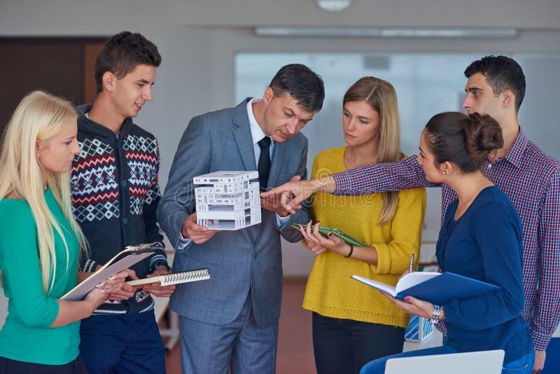 Grupo de estudiantes que trabajan con el profesor en modelo de la casa imagenes de archivo