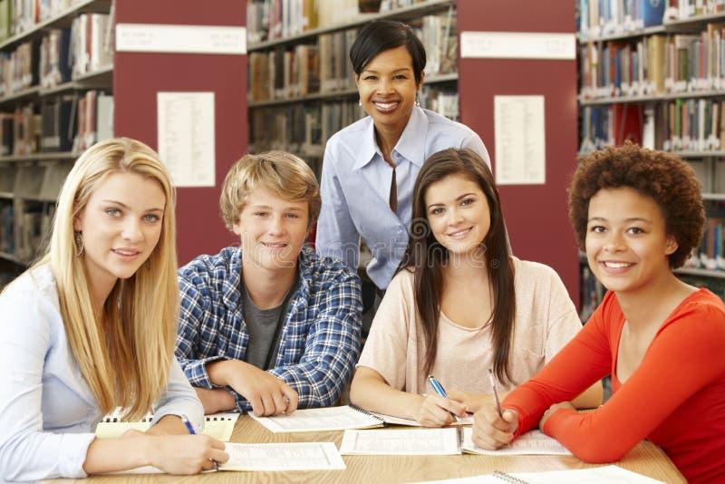 Grupo de estudiantes que trabajan en biblioteca con el profesor fotografía de archivo
