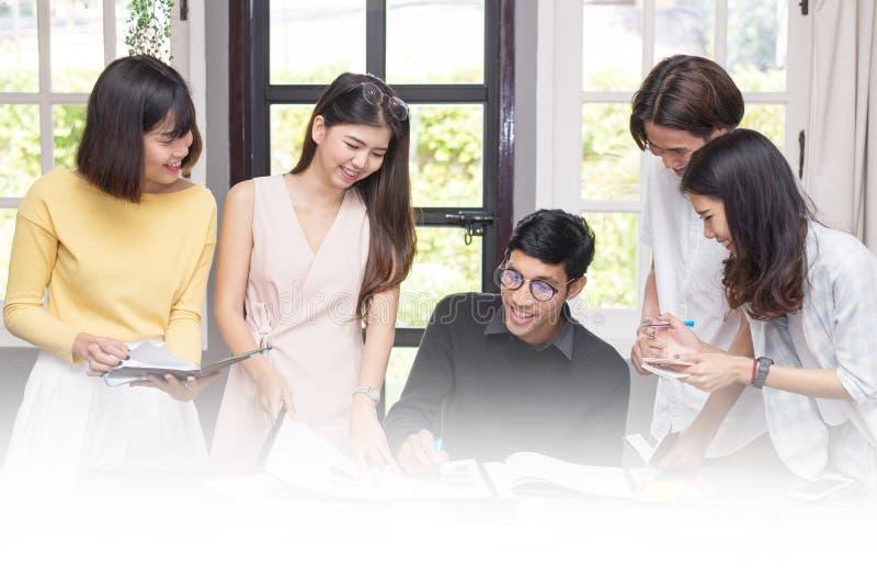 Grupo de estudiantes que usan ideas mientras que estudia junto foto de archivo libre de regalías