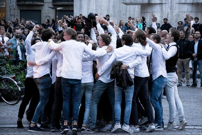 Grupo de estudiantes que van de fiesta en la calle en Amsterdam imagen de archivo