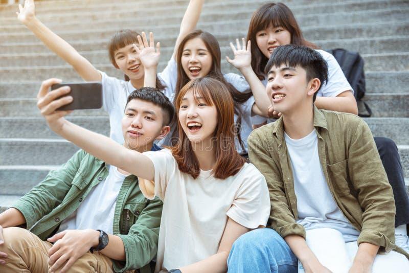 Grupo de estudiantes tomando selfie en las escaleras del campus fotos de archivo libres de regalías