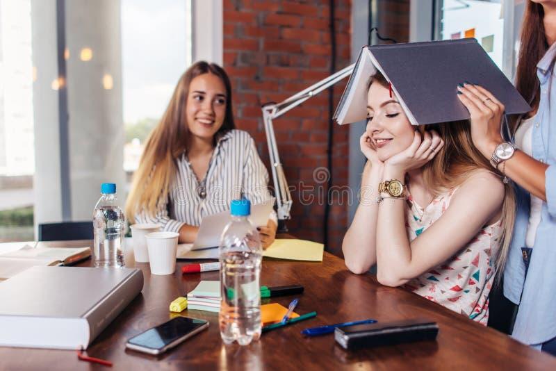 Grupo de estudiantes universitarios alegres que hacen la preparación junta y que hacen el tonto mientras que se sienta en la tabl imágenes de archivo libres de regalías