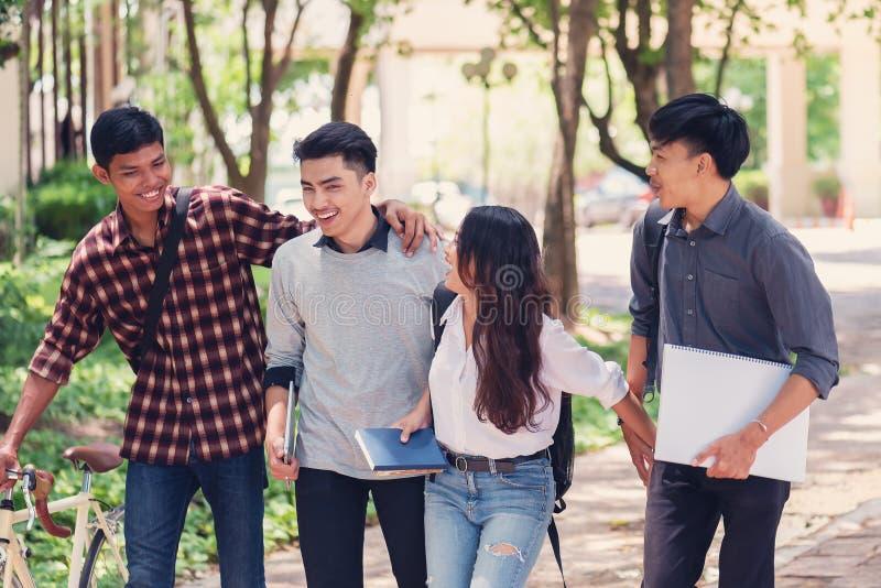 Grupo de estudiantes universitarios que caminan afuera junto en campus, fotos de archivo libres de regalías