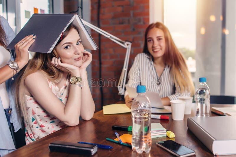 Grupo de estudiantes universitarios que se sientan en la tabla de trabajo en sala de clase foto de archivo