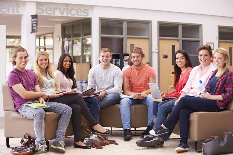 Grupo de estudiantes universitarios que se sientan y que hablan junto fotos de archivo