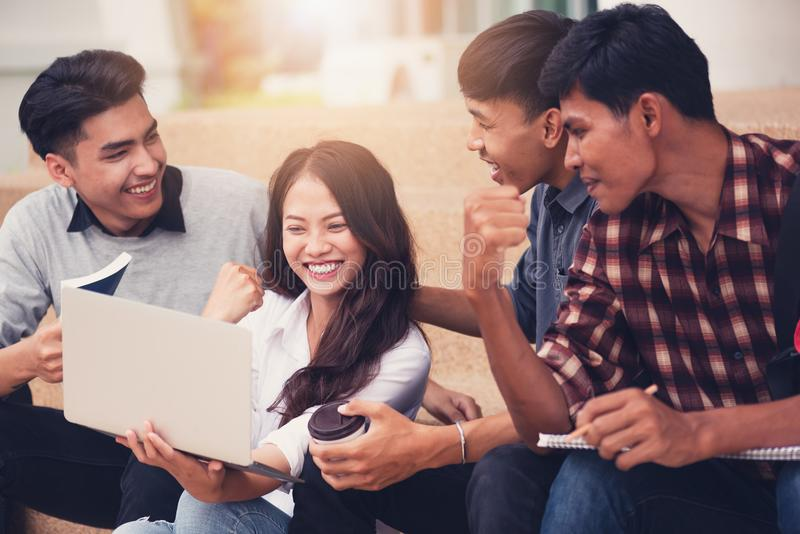 Grupo de estudiantes universitarios que sonríen como utilizan el ordenador portátil imágenes de archivo libres de regalías
