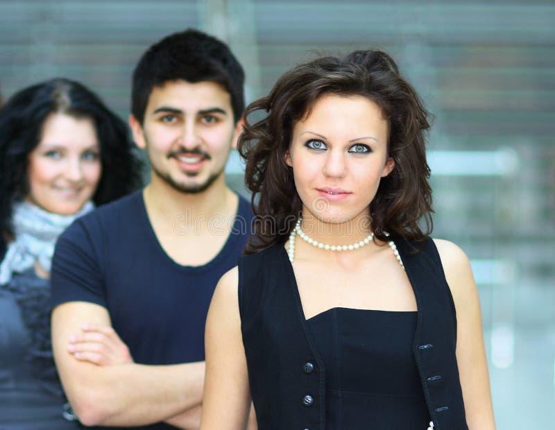 Grupo de estudiantes universitarios que sonríen que se coloca amistoso el uno al otro fotografía de archivo
