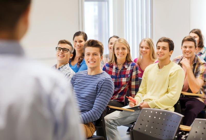 Grupo de estudiantes y de profesor con el cuaderno imagenes de archivo