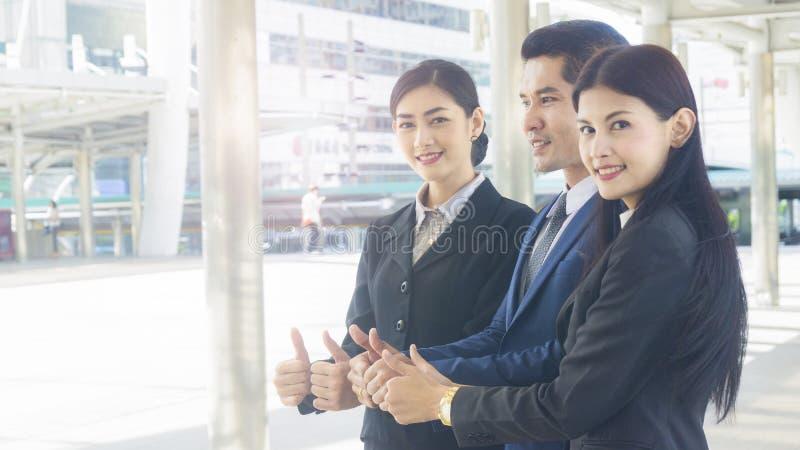 Grupo de executivos do homem e o suporte e o polegar da mulher acima do tog imagens de stock royalty free