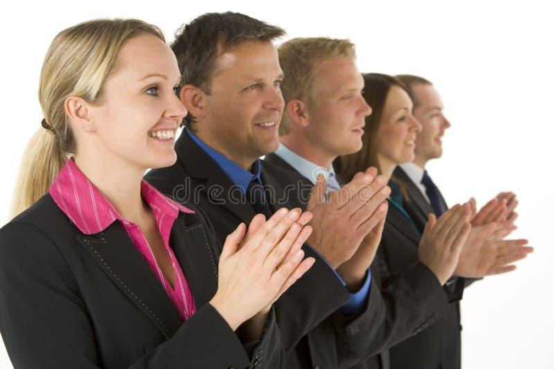 Grupo de executivos em uma linha que aplaudem imagens de stock