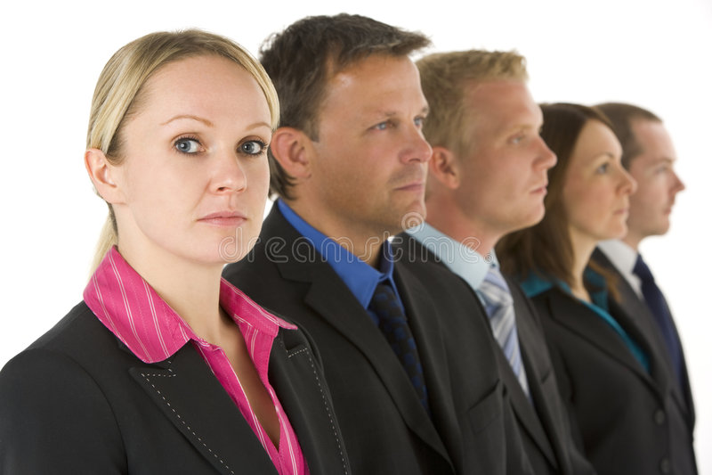 Grupo de executivos em uma linha que olha séria foto de stock