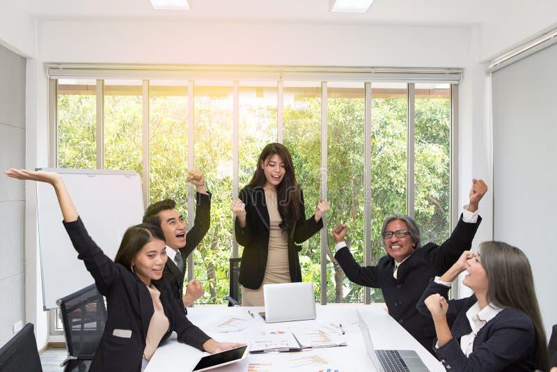 Grupo de executivos felizes que cheering no escritório Comemore o sucesso A equipe do negócio comemora um bom trabalho no escritó imagens de stock royalty free