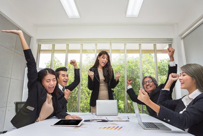 Grupo de executivos felizes que cheering no escritório Comemore o sucesso A equipe do negócio comemora um bom trabalho no escritó foto de stock royalty free