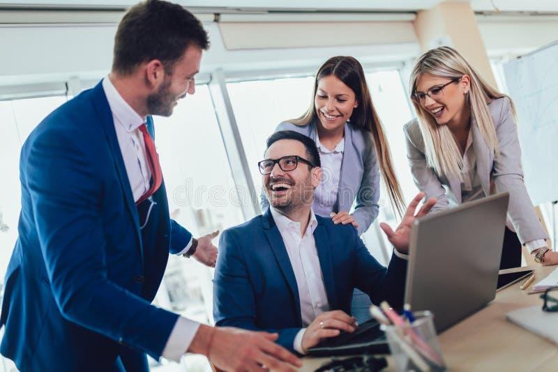 Grupo de executivos novos que trabalham e que usam o portátil ao sentar-se na mesa de escritório junto imagens de stock royalty free