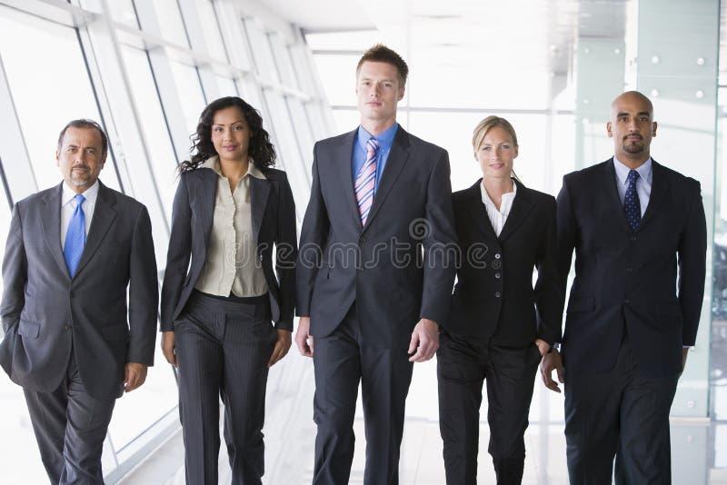 Grupo de executivos que andam para a câmera imagem de stock