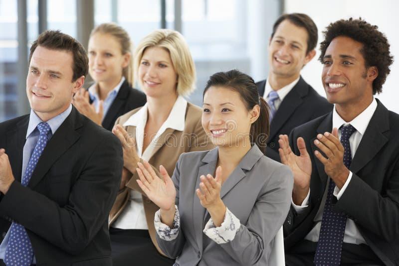 Grupo de executivos que aplaudem o orador no fim de uma apresentação imagens de stock