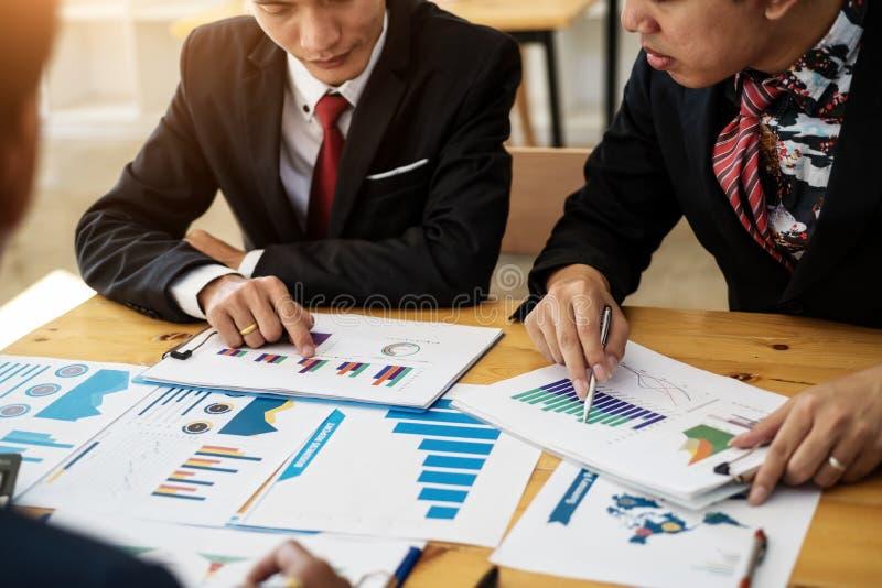 Grupo de executivos que discutem o plano do projeto junto com a análise do relatório financeiro dos dados na sala de reunião cont imagens de stock