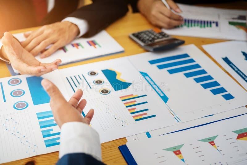 Grupo de executivos que discutem o plano do projeto junto com a análise do relatório financeiro dos dados na sala de reunião cont fotografia de stock