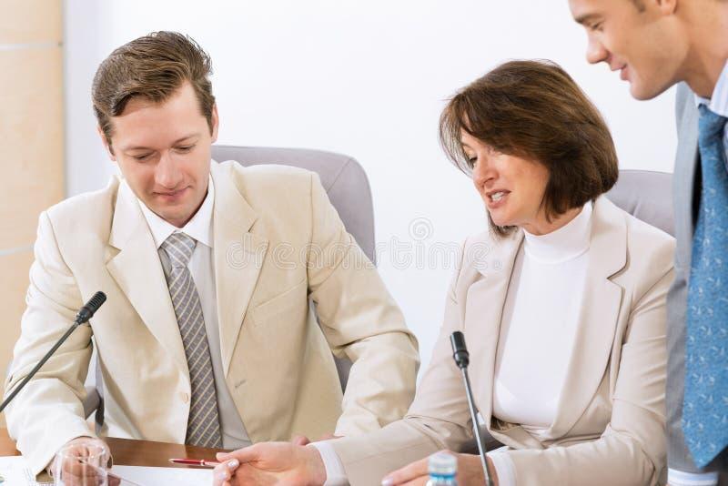 Grupo de executivos que discutem originais foto de stock royalty free