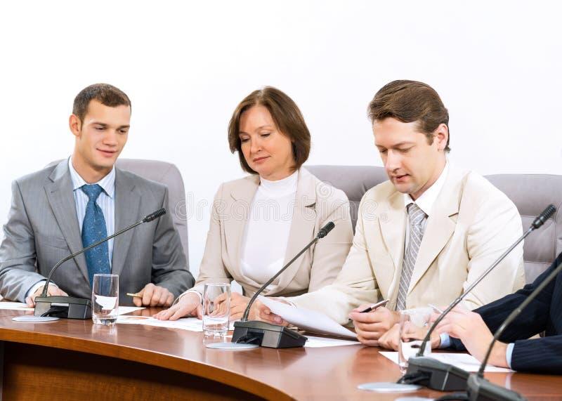 Grupo de executivos que discutem originais imagem de stock