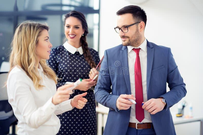 Grupo de executivos que discutem os detalhes os mais atrasados sobre o projeto no escritório foto de stock royalty free