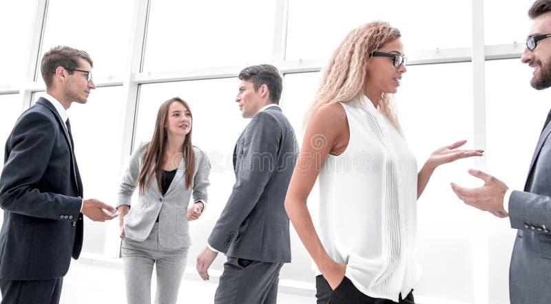 Grupo de executivos que discutem suas ideias que estão em um corredor do escritório foto de stock