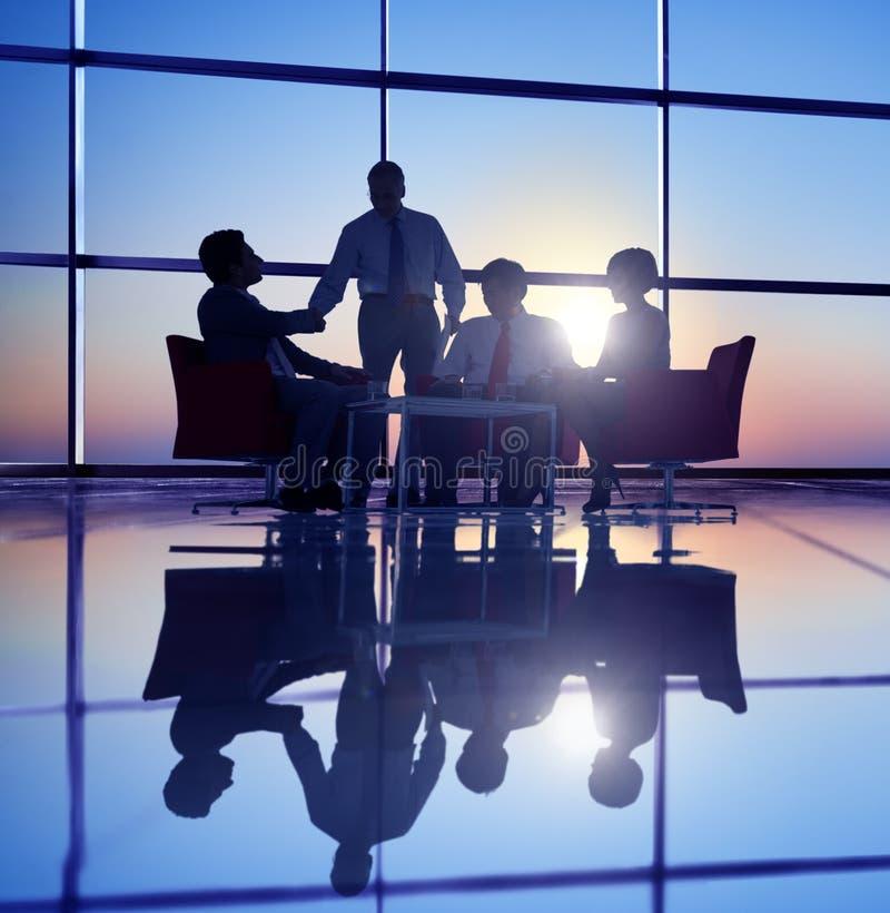 Grupo de executivos que encontram-se no Lit traseiro foto de stock royalty free