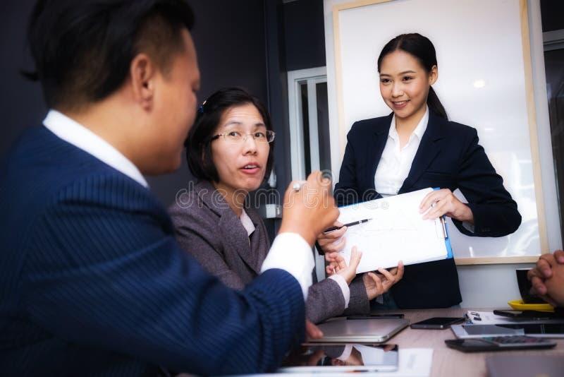 Grupo de executivos que encontram-se sobre os economistas que trabalham analisando cartas do investimento Local de trabalho de en imagem de stock royalty free