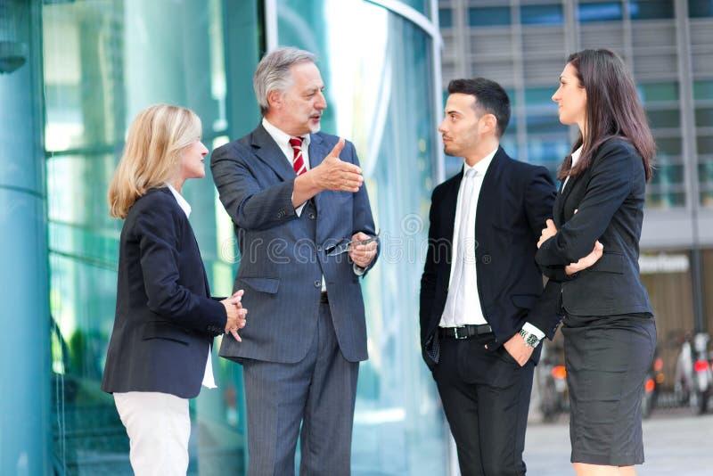 Grupo de executivos que falam exterior imagens de stock