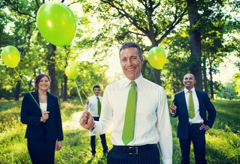Grupo de executivos que guardam balões na floresta fotos de stock