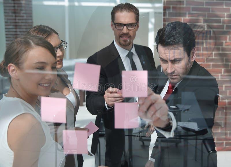 Grupo de executivos que leem notas do negócio em uma placa de vidro fotos de stock