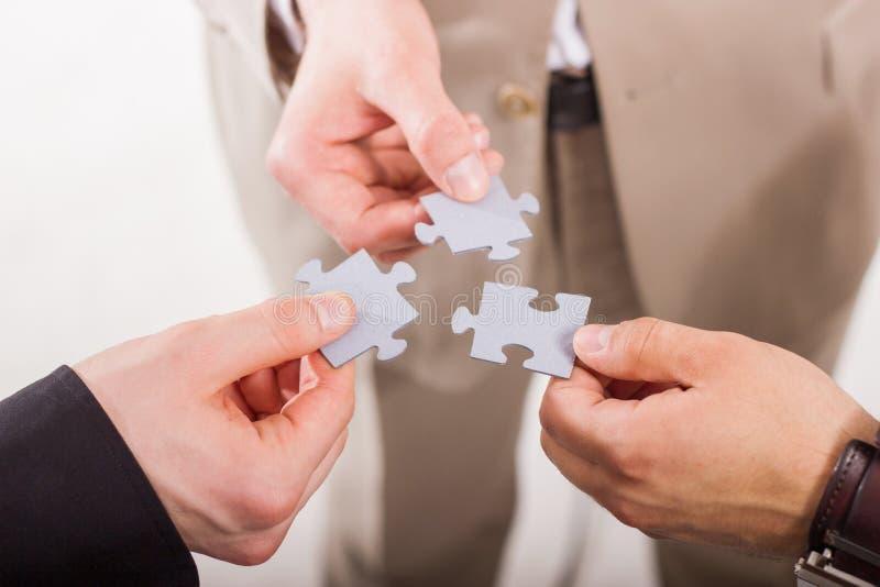 Grupo de executivos que montam o enigma de serra de vaivém. Trabalhos de equipa. foto de stock royalty free