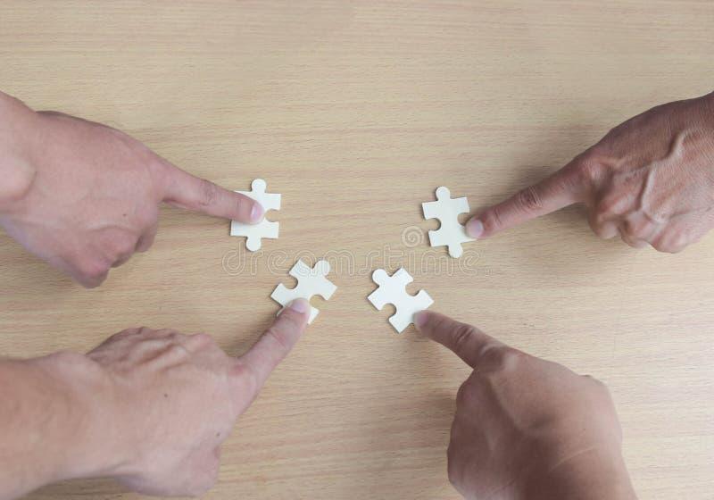 Grupo de executivos que montam o enigma de serra de vaivém que quer unir partes de enigma sobre o backgroung de madeira da tabela foto de stock royalty free