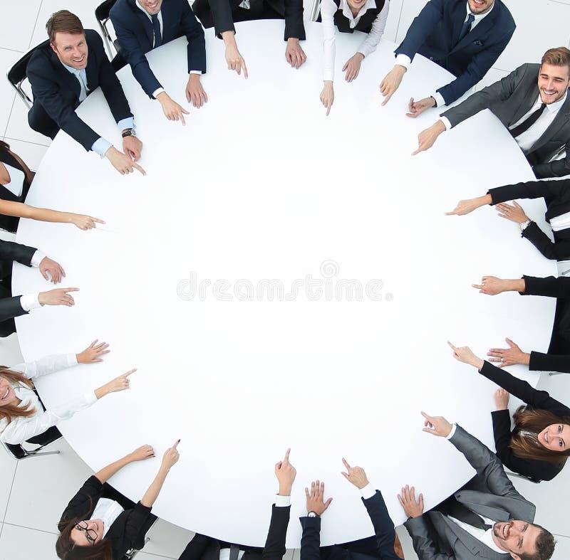 Grupo de executivos que sentam-se na mesa redonda O conceito do negócio ilustração stock