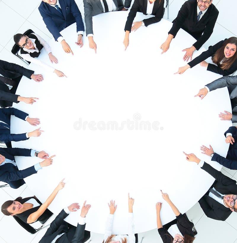 Grupo de executivos que sentam-se na mesa redonda O conceito do negócio ilustração royalty free