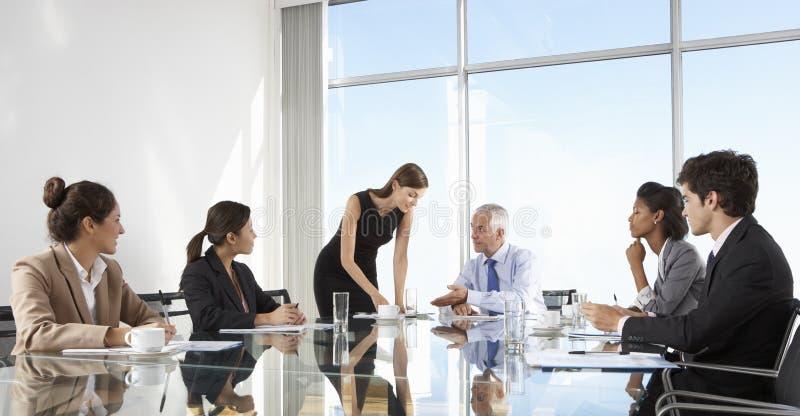 Grupo de executivos que têm a reunião da direção em torno da tabela de vidro fotos de stock royalty free
