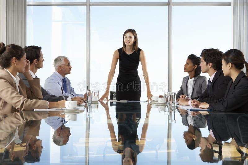 Grupo de executivos que têm a reunião da direção em torno da tabela de vidro imagem de stock