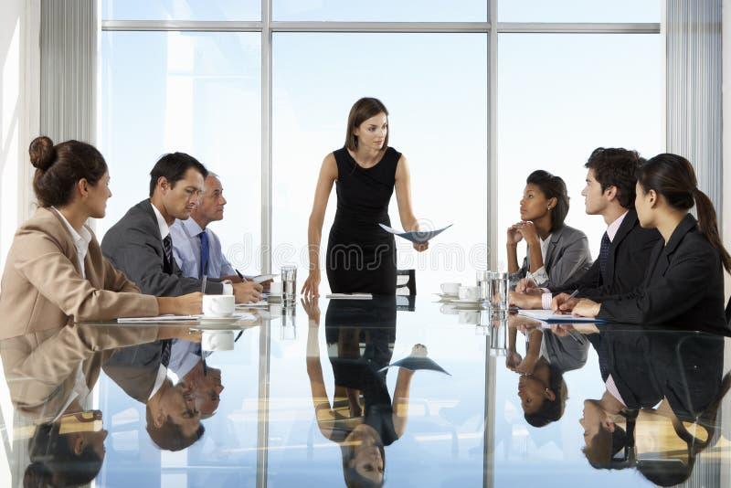 Grupo de executivos que têm a reunião da direção em torno da tabela de vidro imagens de stock