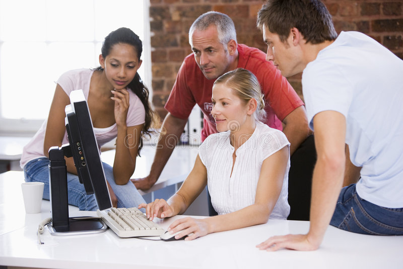 Grupo de executivos que trabalham em torno do computador fotografia de stock royalty free