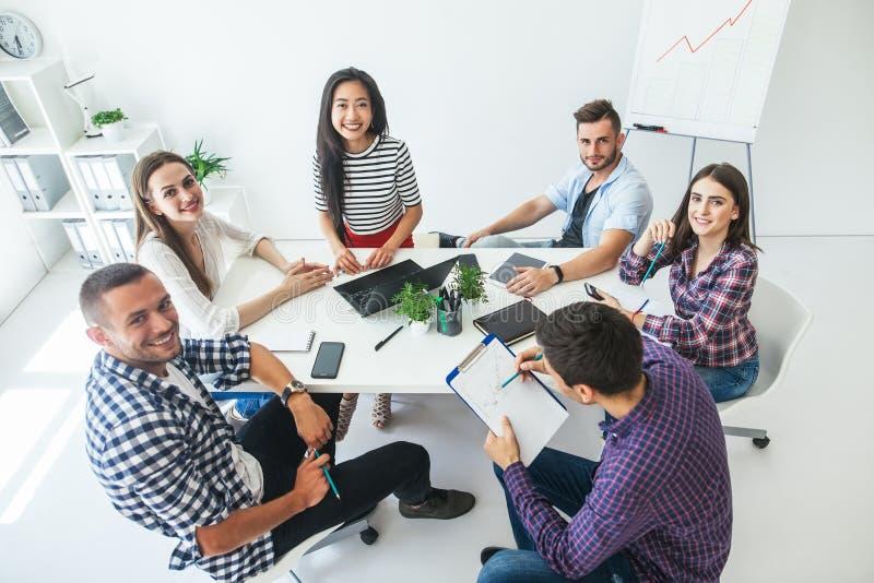 Grupo de executivos de sorriso que trabalham no escritório imagens de stock