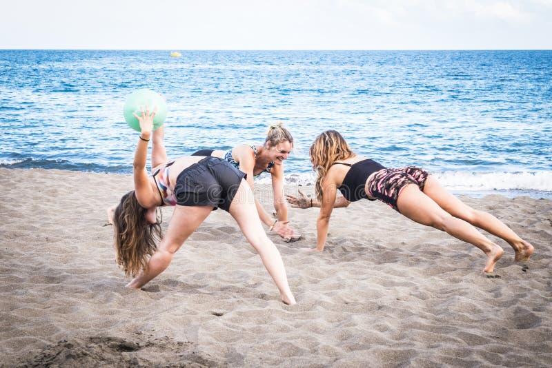 Grupo de exercícios e de pilates atrativos caucasianos do woind das meninas na costa no oceano férias e fazer saudável do estilo  fotos de stock