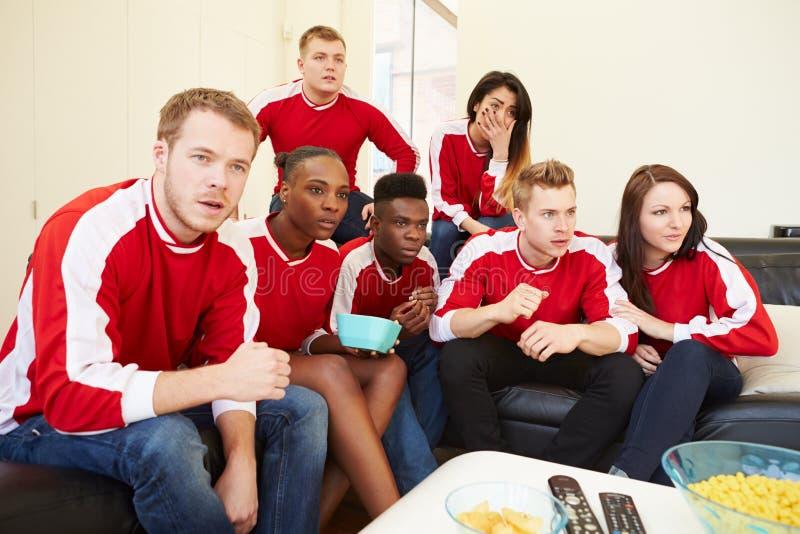 Grupo de fãs de esportes que olham o jogo na tevê em casa foto de stock royalty free