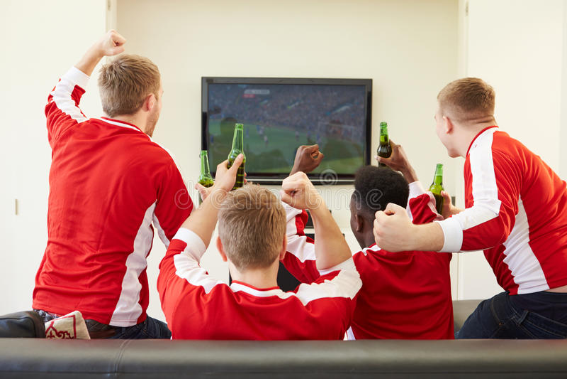 Grupo de fãs de esportes que olham o jogo na tevê em casa fotos de stock royalty free