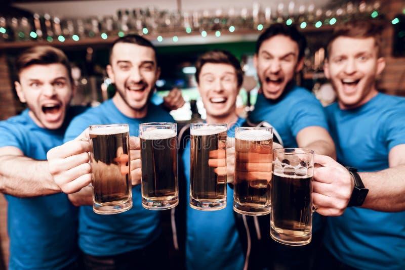 Grupo de fãs de esportes que bebem a cerveja que comemora e que cheering na barra de esportes imagem de stock royalty free