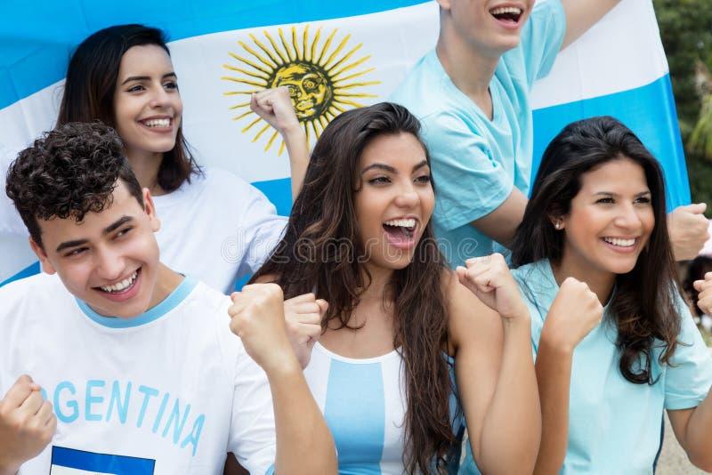 Grupo de fãs de futebol cheering de Argentina com fl argentino imagem de stock