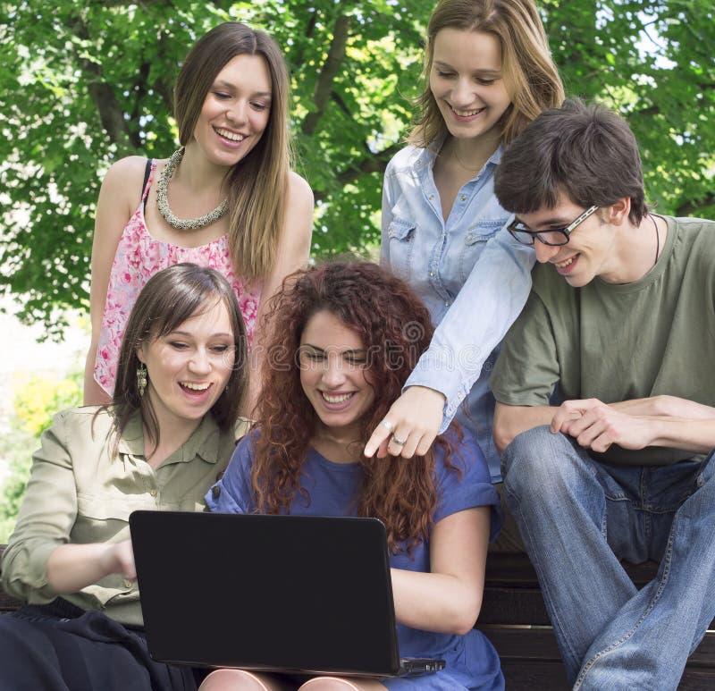 Grupo de faculdade/estudantes universitário com portátil fotografia de stock royalty free