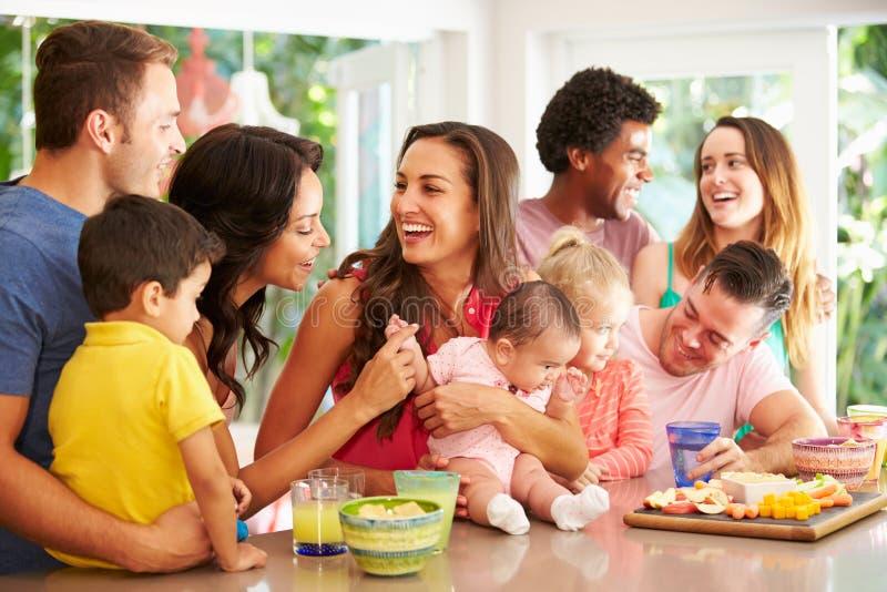 Grupo de famílias que apreciam petiscos em casa imagens de stock