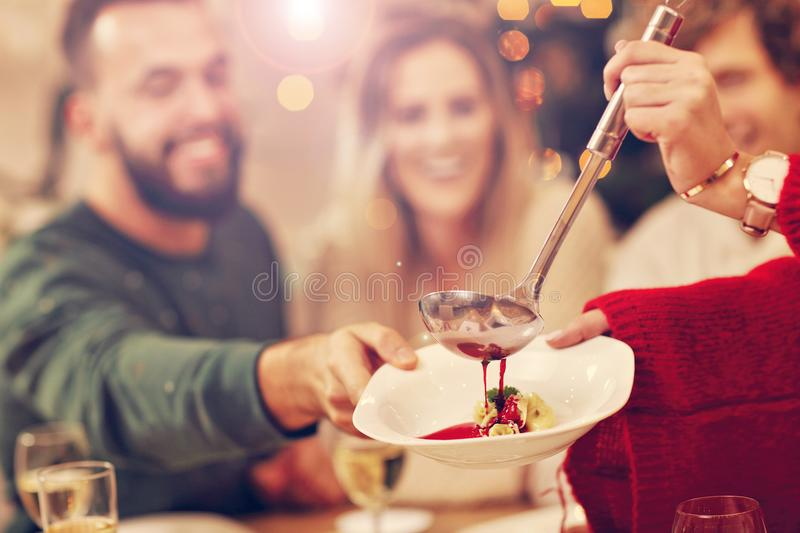Grupo de familia y de amigos que celebran la cena de la Navidad imagen de archivo