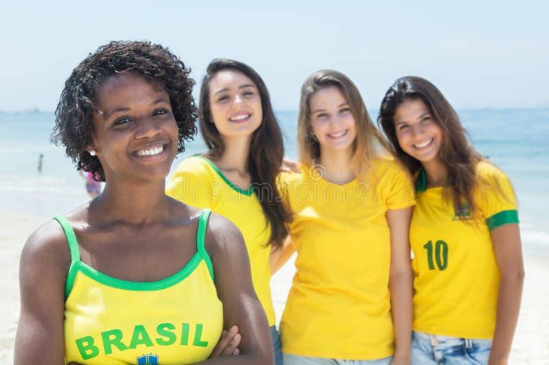 Grupo de fans de deportes brasileñas en la playa fotografía de archivo
